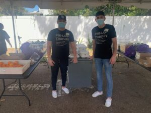 Steven and Andrew stand under a pop up tent, between two tables, in front of a cart. They both wear facemasks and their WestCMR philanthropy tee shirts.