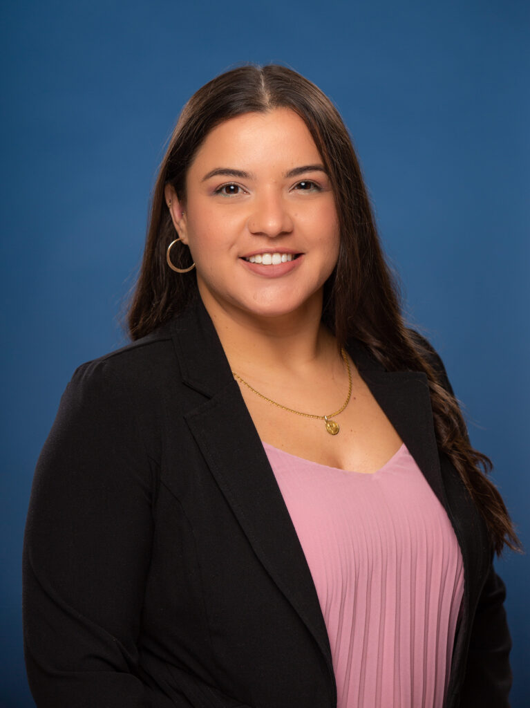 Jenny is pictured wearing a pink pleated top and black blazer. She is photographed in front of a blue background.